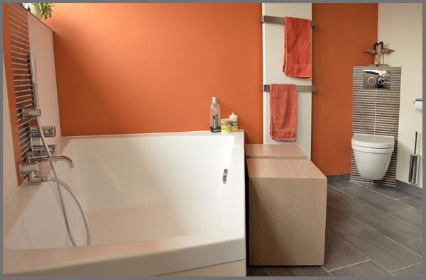 ruime badkamer met schuin ligbad en een oranje geschilderde wand