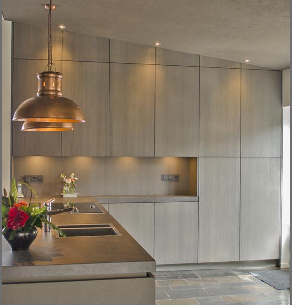 Extra werkblad in een met het plafond mee afgeschuinde kastenwand, geeft een optisch vergrotend effect
